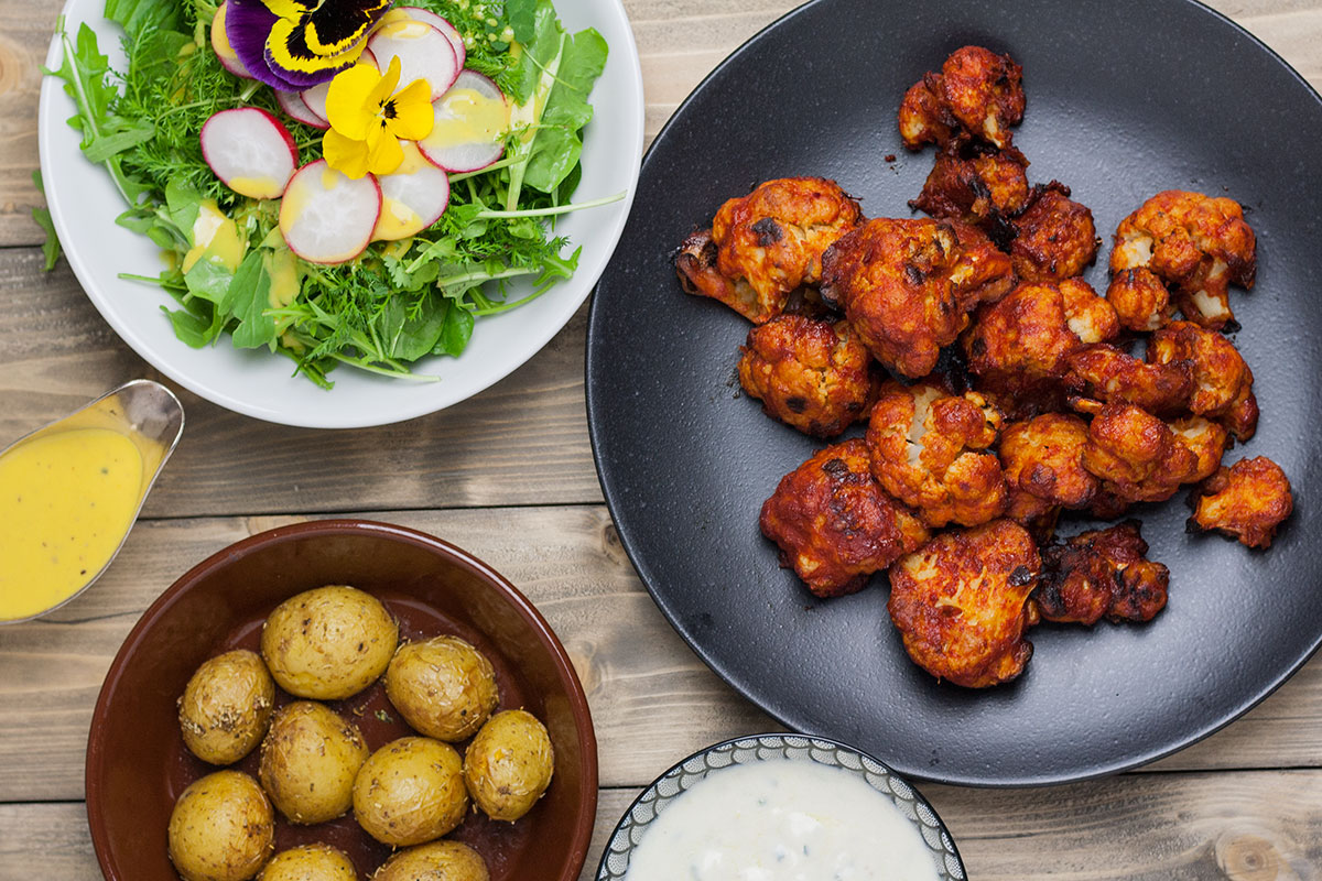 vegane Buffalo Wings aus Blumenkohl mit Kartoffeln und Salat