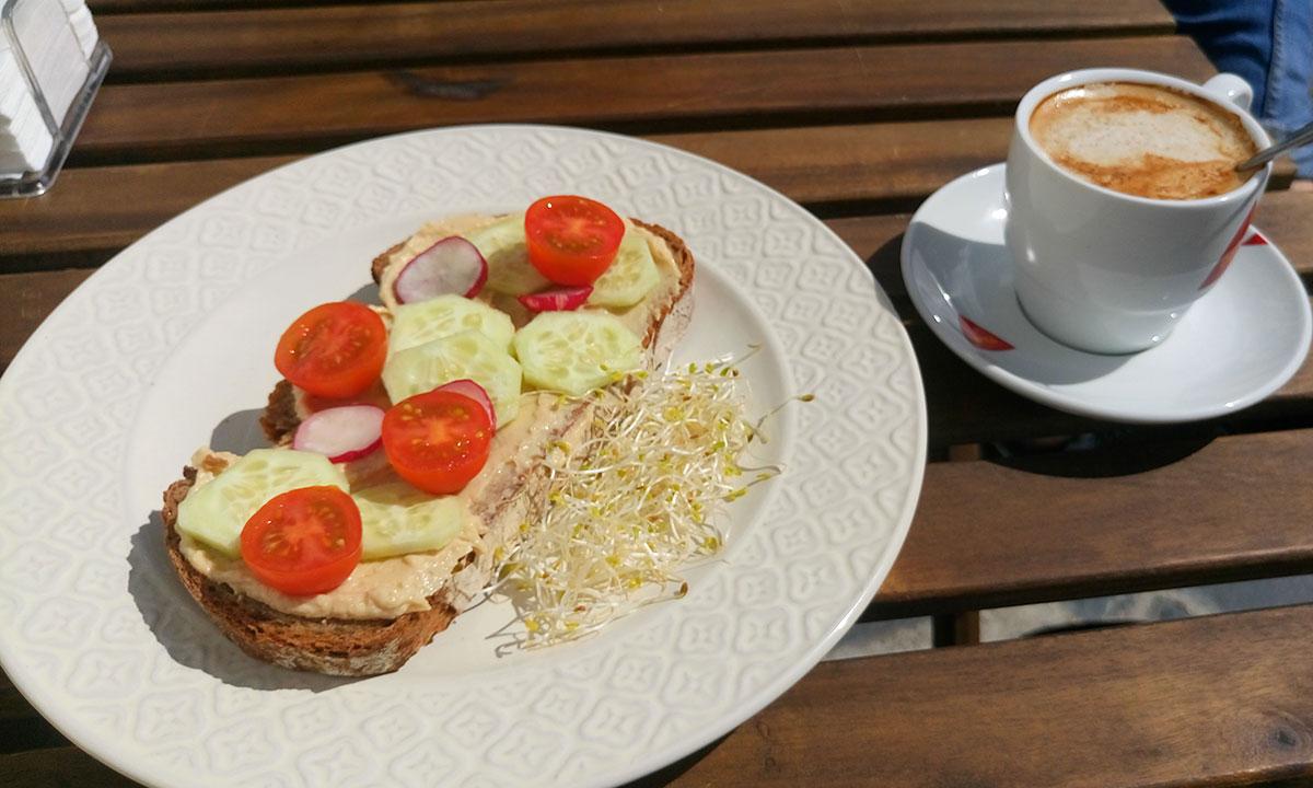 vegan belegtes Brot und Cappucino mit Mandelmilch