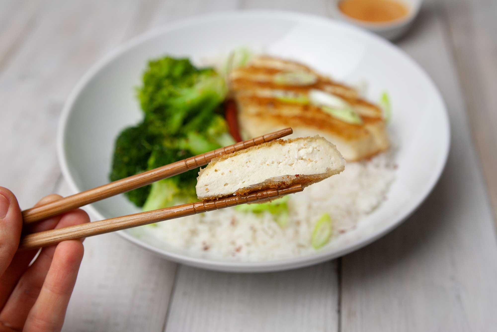 paniertes Tofufilet wird zusammen mit Reis und Erdnusssoße serviert