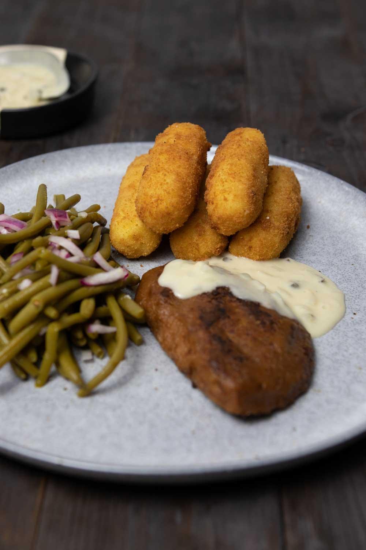 Vegane Kroketten serviert mit Seitanschnitzel, Soße und Bohnensalat
