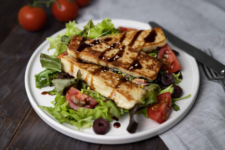 gebratener veganer Halloumi serviert auf einem Salat