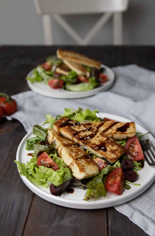 veganer Halloumi angebraten und serviert auf Salat