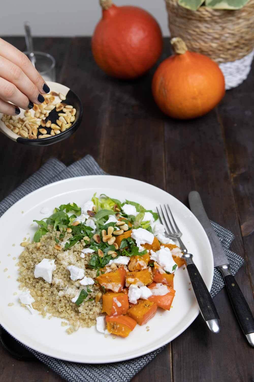 Veganes Herbstgericht aus gebackenem Kürbis, Quinoa, Pinienkernen und veganem Feta