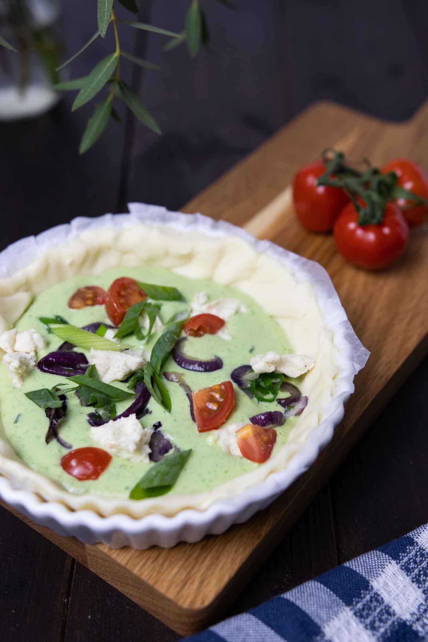 Vegane Quiche wird mit Bärlauch und Gemüse gefüllt